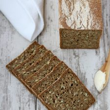 Slices of rye bread and a wooden knife with butter on a wooden surface