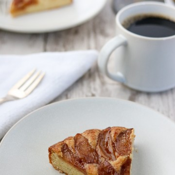 A slice of Swedish apple cake with a fork, napkin and a cup of coffee