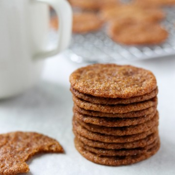 A close up of a stack of Swedish ginger snaps and a cup of coffee