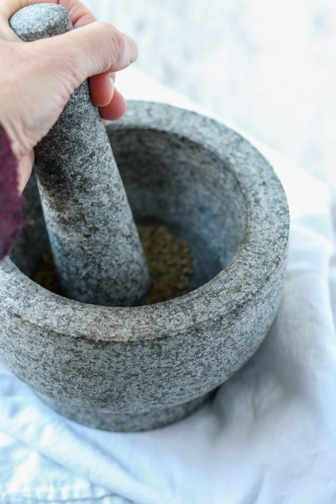 A person crushing cardamom in a mortar with a pestle