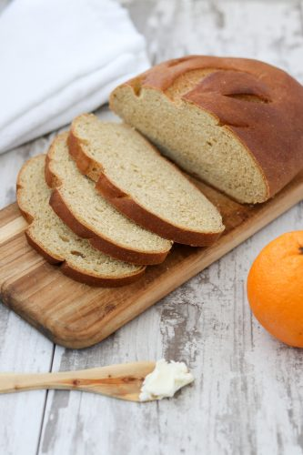 Sliced limpa bread on top of a wooden cutting board next to an orange
