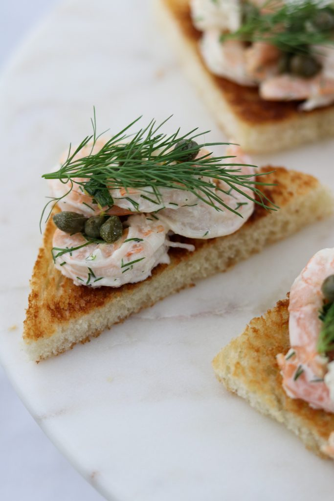 A close up of shrimp salad on toast with capers and dill