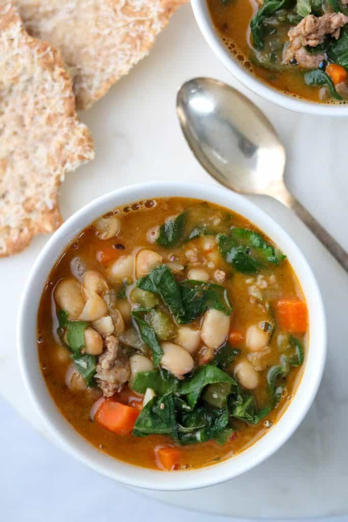 A bowl of white bean and sausage soup with Swiss chard with a spoon and crispbread