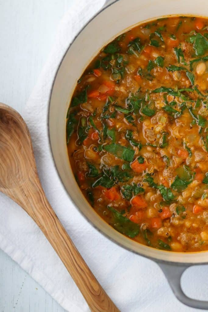 A pot of white bean and sausage soup with swiss chard and a wooden ladle