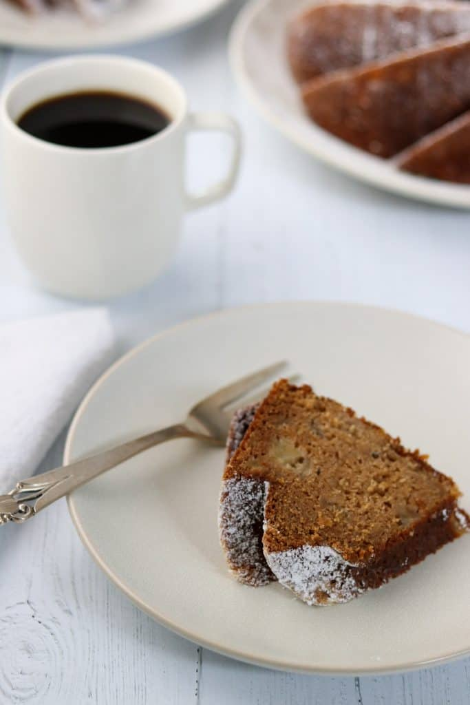 A slice of pear cardamom bundt cake on a plate with a fork and a cup of coffee