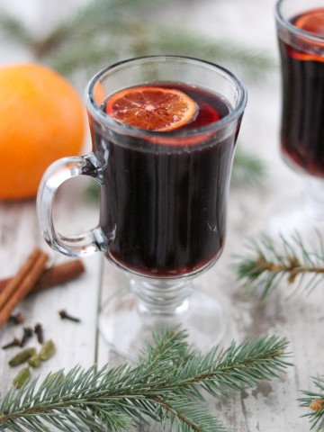 A glass of Swedish glögg with cinnamon, evergreen branches and an orange
