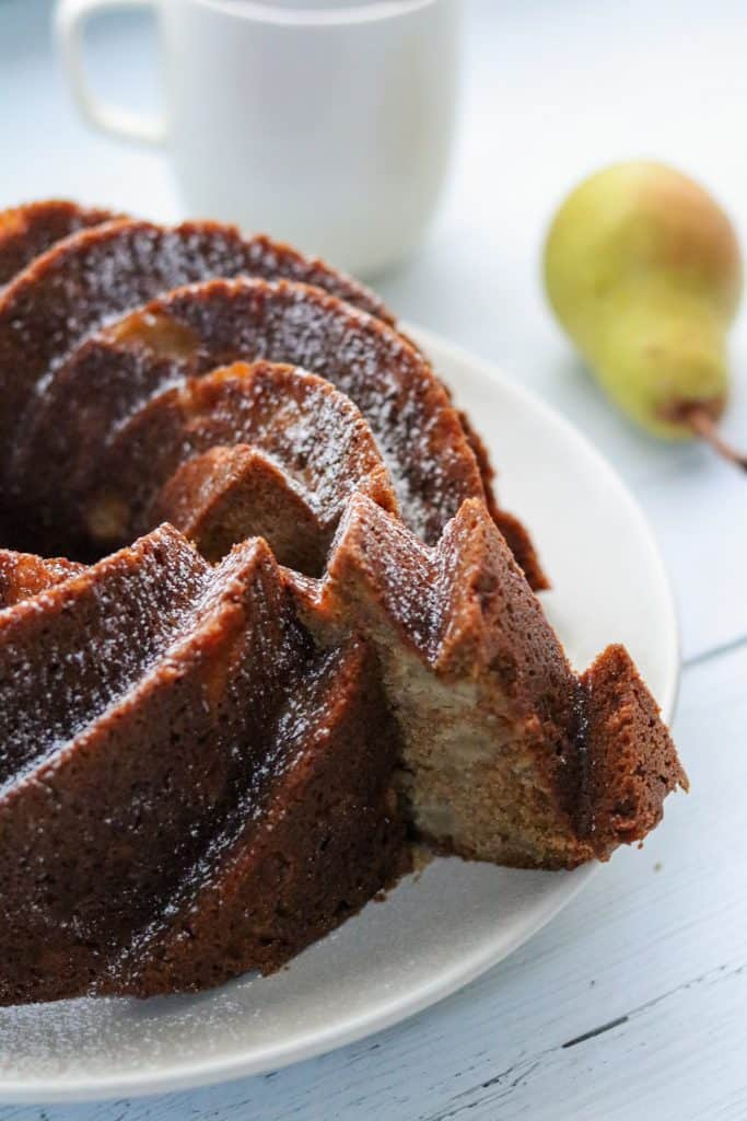 A close up of a slice of pear cardamom bundt cake being removed from the whole cake on a plate