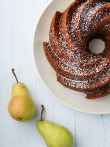 A pear cardamom bundt cake on a plate with two pears