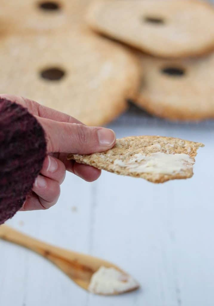 A person holding a buttered piece of crispbread