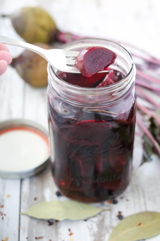 A jar filled with pickled beets and a fork