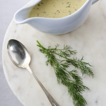 Creamy mustard dill sauce in a gravy boat with a spoon and fresh dill on a marble surface