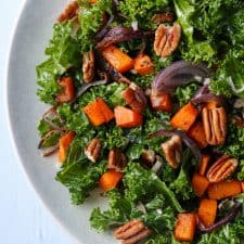 Kale salad with roasted butternut squash and pecans on a plate