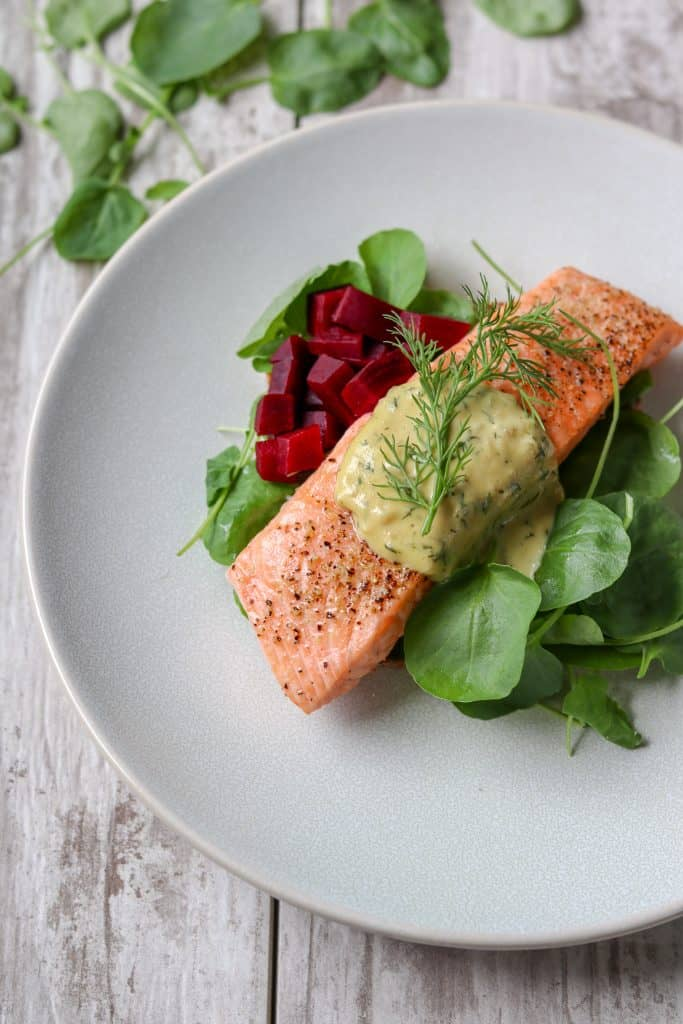 Roasted salmon topped with creamy mustard sauce, pickled beets and greens on a plate
