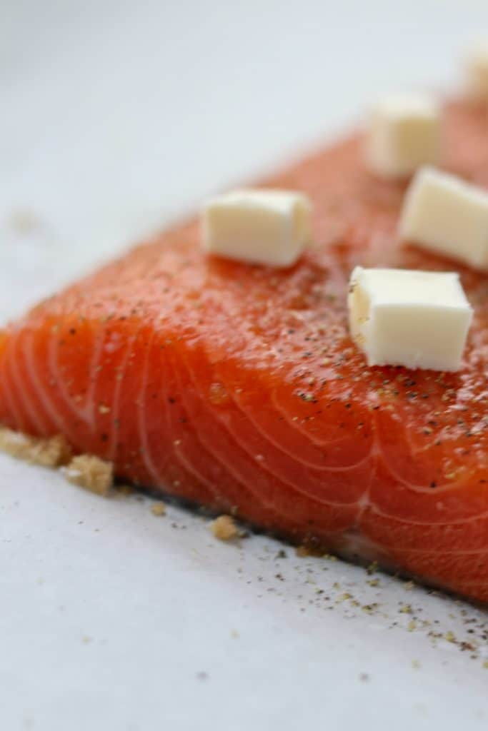 A close up of raw salmon topped with cubes of butter