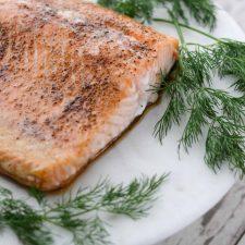 A piece of salmon on a plate with fresh dill
