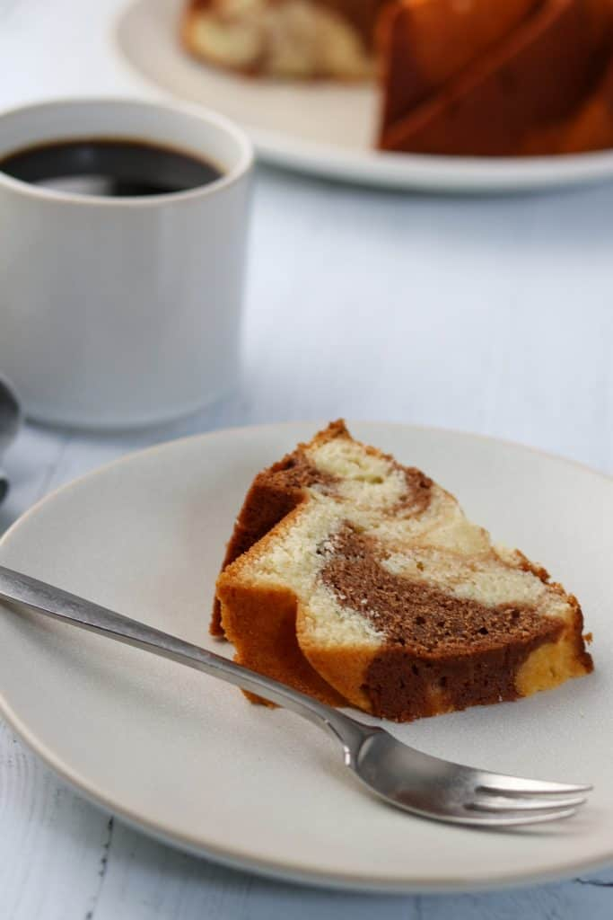 A slice of marbled almond tiger cake on a plate with a fork and a cup of coffee