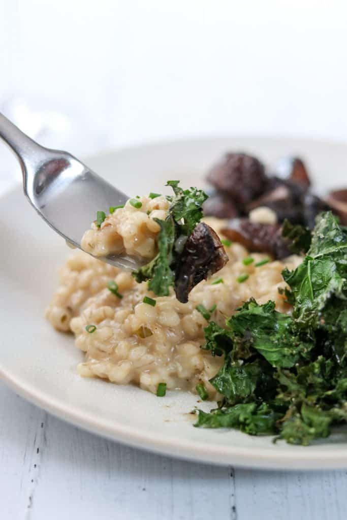 A close up of a bite of barley risotto, mushroom and kale on a fork