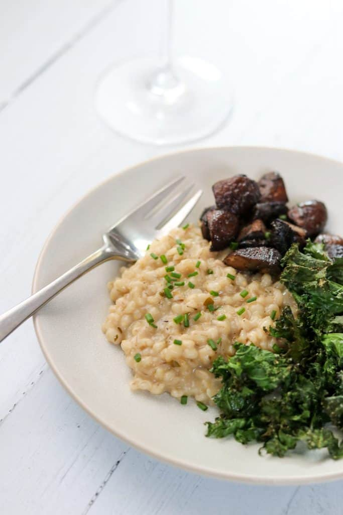 A plate of barley risotto, roasted mushrooms and kale on a wood surface with a wine glass