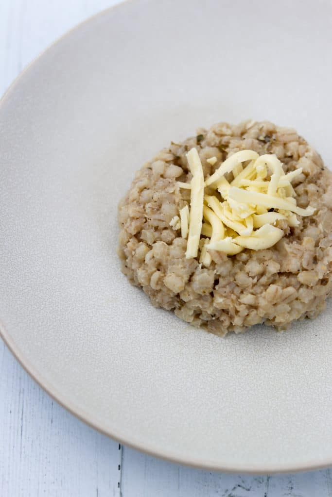 An uncooked barley risotto cake topped with cheese