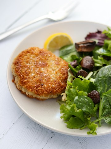 A risotto cake, salad and lemon wedge on a plate with a fork