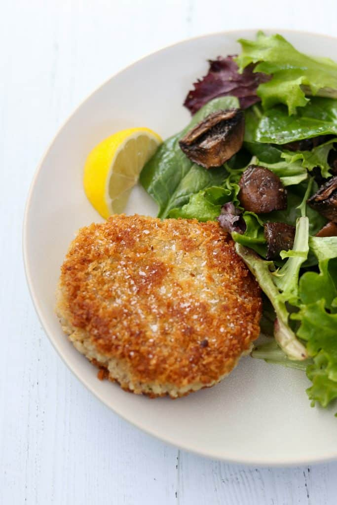 A barley risotto cake with salad and a lemon wedge on a plate