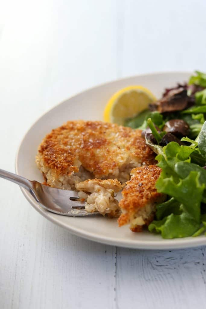 A barley risotto cake, salad and lemon wedge on a plate with a fork