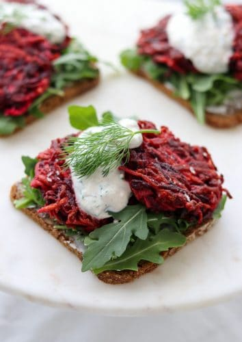 An open sandwich with beet and celery root cakes and creamy sauce on a plate