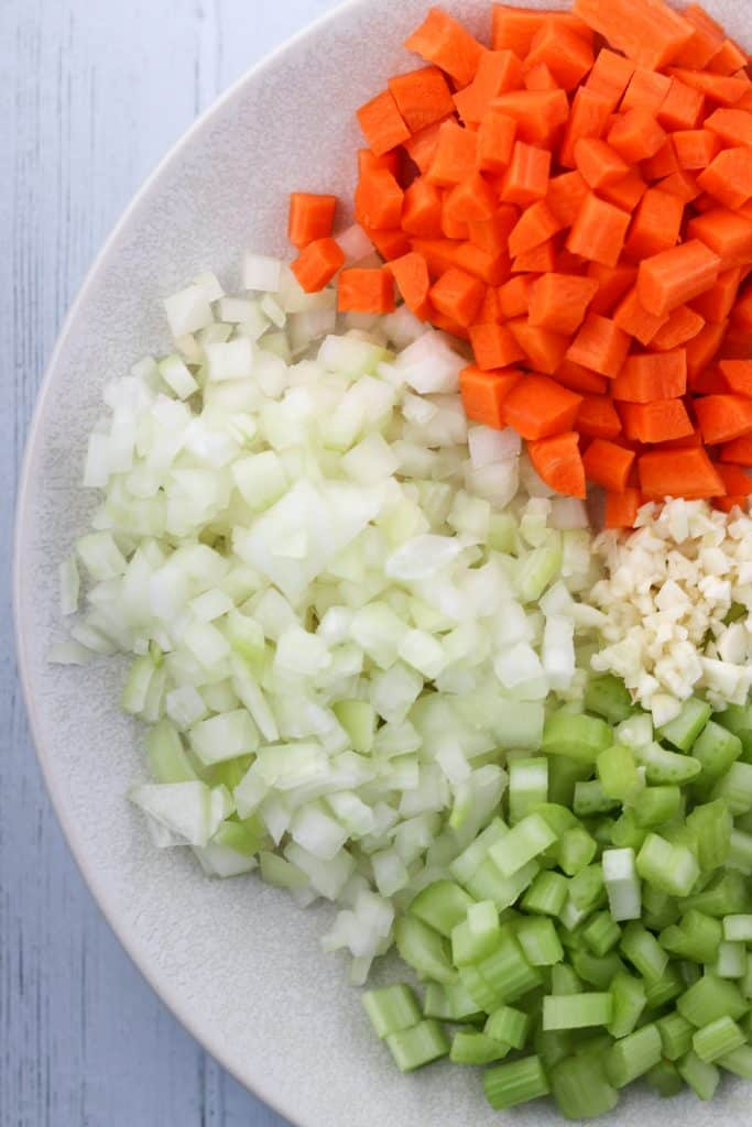 Chopped onion, carrot, celery and garlic on a plate