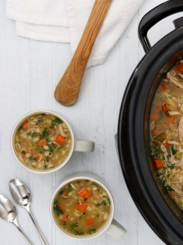 Chicken soup in a crockpot with two mugs of soup, spoons and a wooden ladle