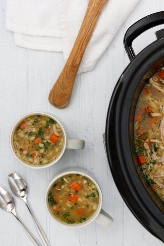 Chicken soup in a crockpot next to two mugs of soup, spoons and a ladle