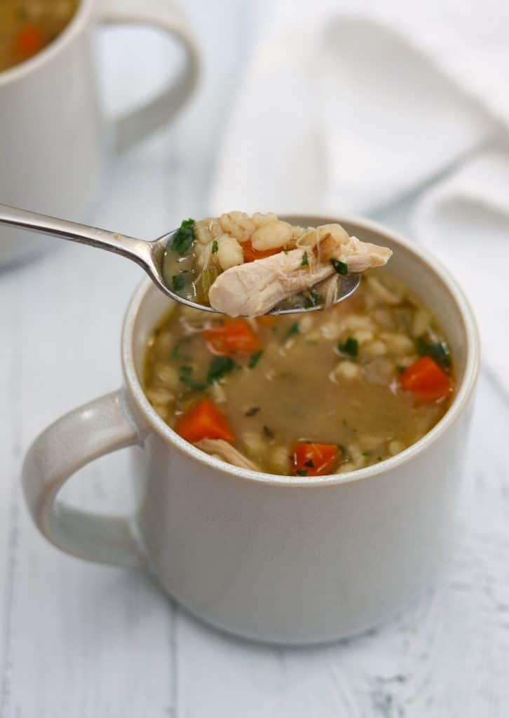 A close up of a mug of chicken soup with a spoon
