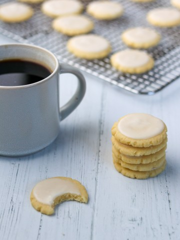 A stack of lemon cookies and one with a bite out of it next to a cup of coffee