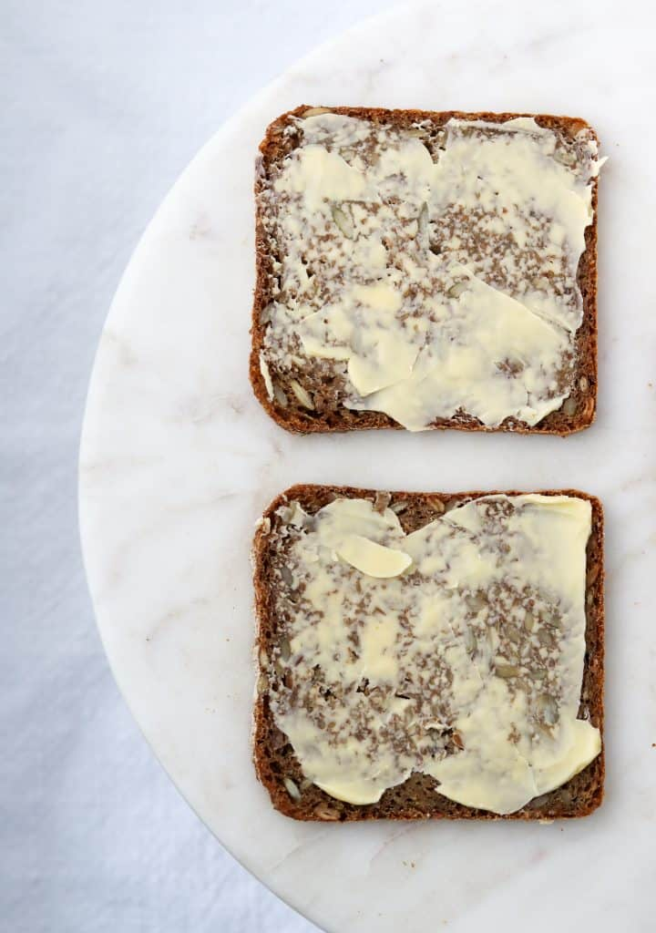 Two pieces of buttered rye bread on a plate
