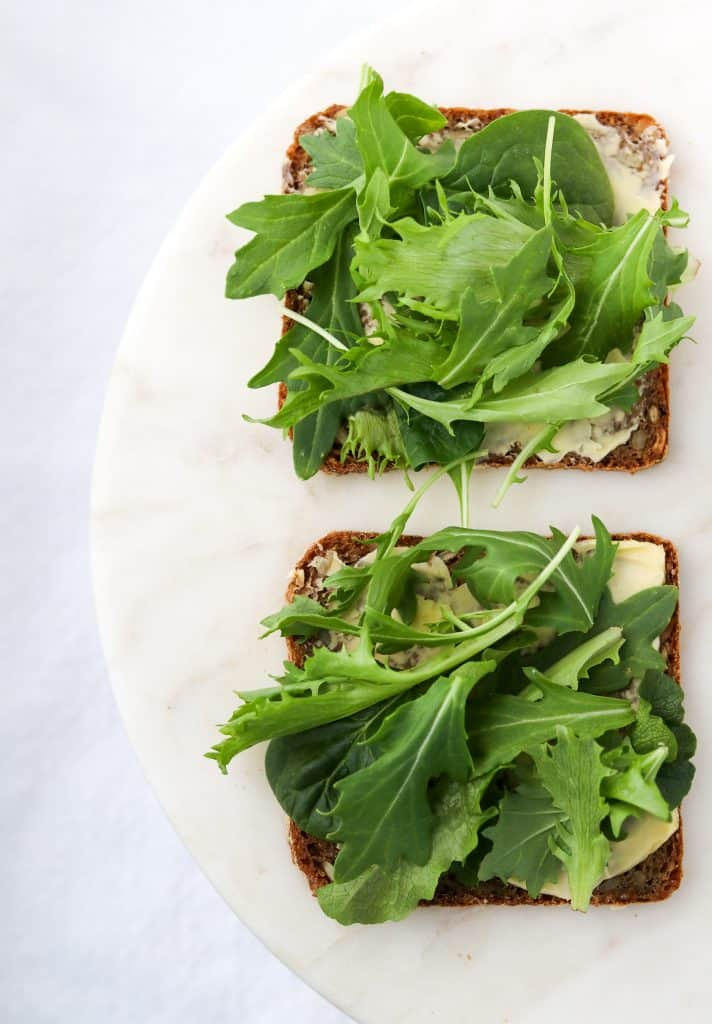 Rye bread topped with butter and lettuce on a plate