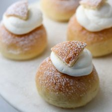 A close up of semlor buns topped with whipped cream on a plate