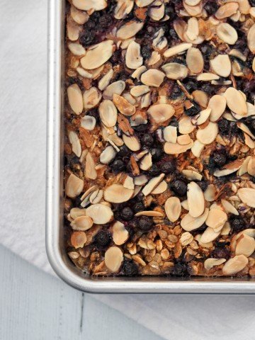 Baked oat and rye porridge with blueberries and almonds in a pan