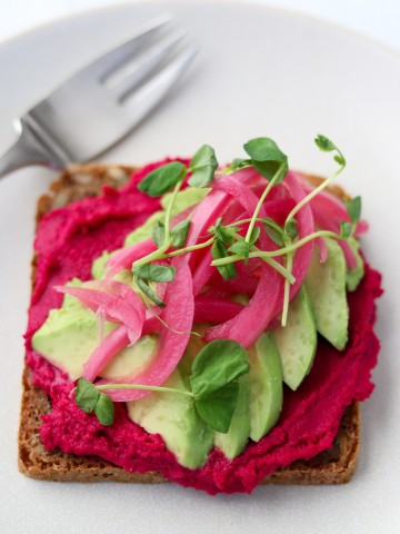 An open sandwich with beet hummus, avocado slices and pickled onions on a plate with a fork