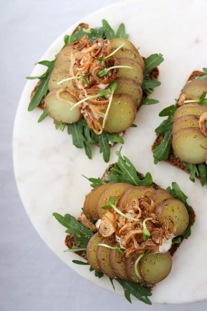 Open sandwiches with lettuce, potato slices, crispy shallots and creamy sauce on a plate