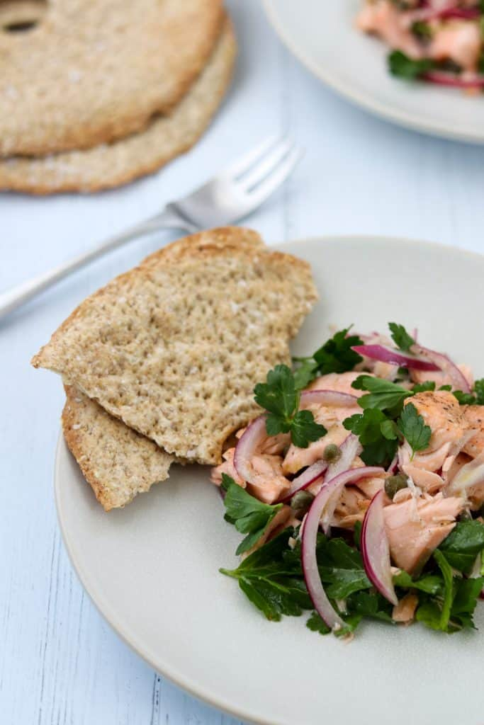 Salmon salad on a plate with crispbread next to a fork