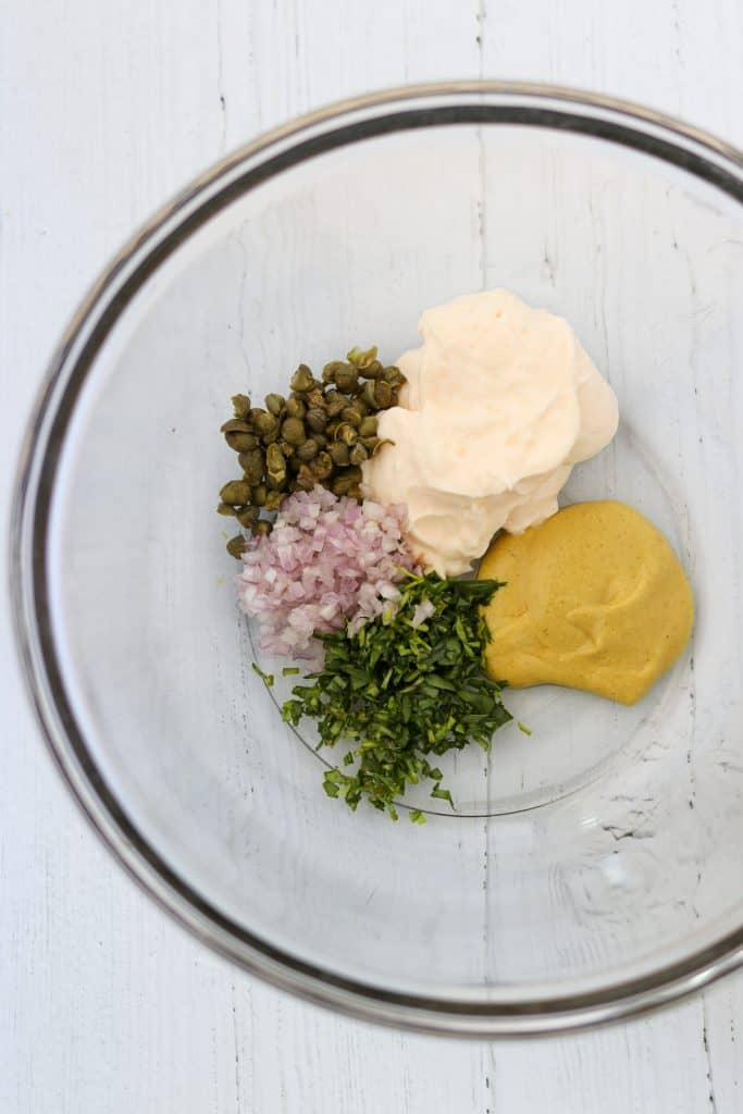 A bowl with mayonnaise, mustard, capers, shallots and herbs