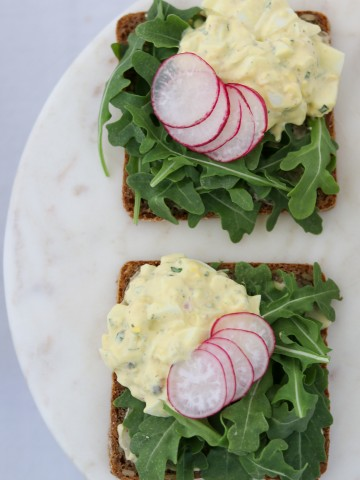 Two open face egg salad sandwiches topped with lettuce and radishes on a plate
