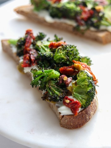 An open sandwich with ricotta cheese, broccoli and sun-dried tomatoes on a plate