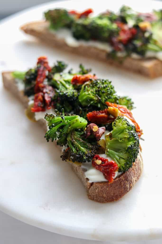A close up of an open sandwich with ricotta, broccoli and sun-dried tomatoes