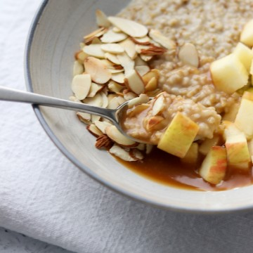 Oatmeal in bowl topped with apple, sliced almonds and caramel sauce with a spoon