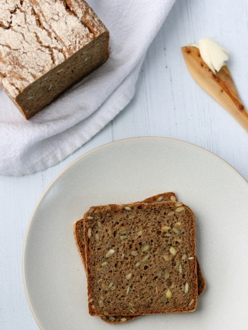 Rye bread slices on a plate next to a loaf of rye bread and a wooden knife with butter