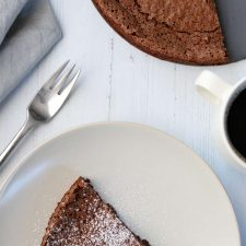 A piece of chocolate cake next to a fork, napkin and cup of coffee