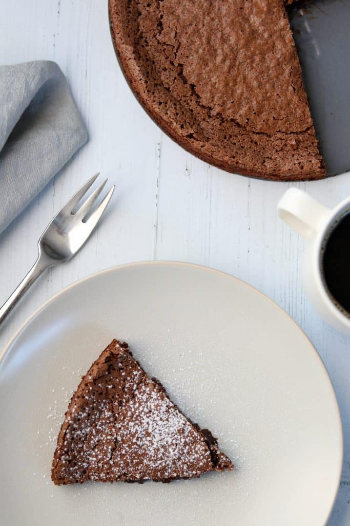 A piece of chocolate cake on a plate next to a fork, napkin and cup of coffee