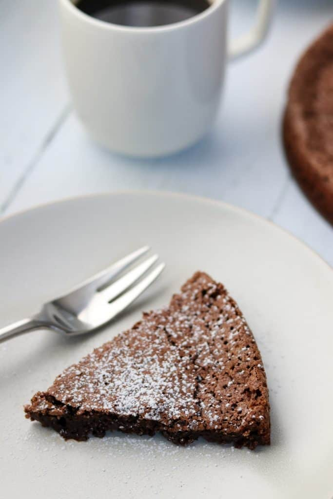 A piece of chocolate cake on a plate with a fork and a mug