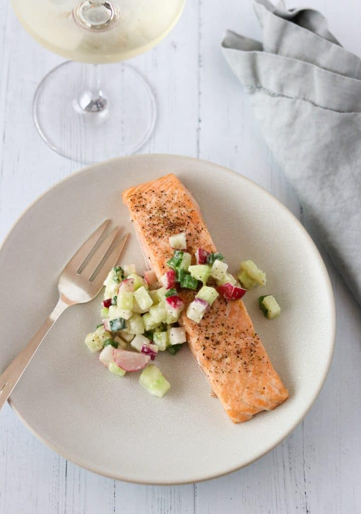 Salmon and cucumber radish relish on a plate with a fork, wine glass and napkin