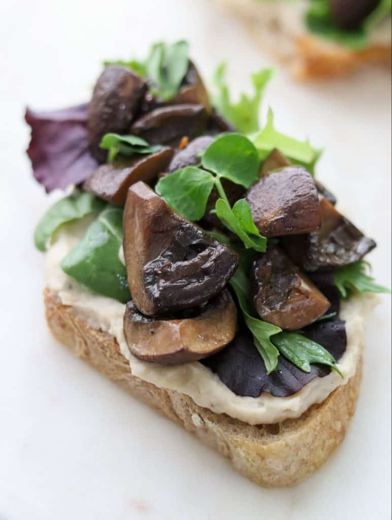 A close up of an open sandwich with mushrooms and lettuce on a plate